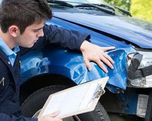 een man controleert de schade van een voertuig